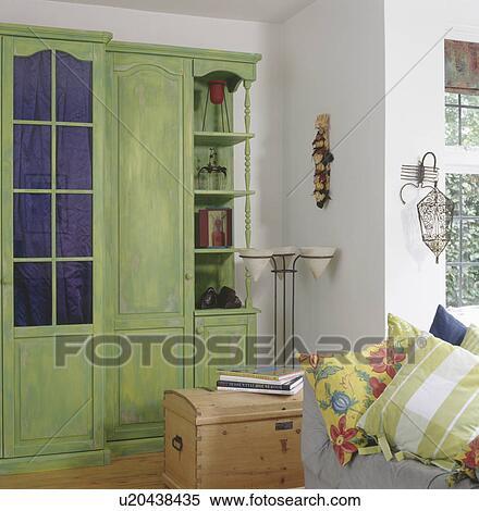 Groot Groene Verontruste Verf Effect Kast In Woonkamer Met Houten Borst Patterned Kussens Op Sofa Stock Fotografie