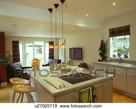 Stock photograph of halogen hob in island unit below pendant halogen hob in island unit below pendant lighting in modern white kitchen aloadofball Images