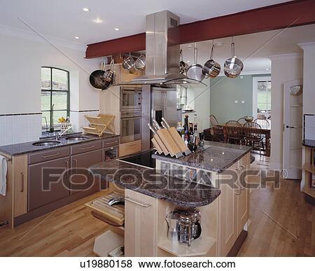 Knife Block On Island Unit With Black Granite Worktop In Modern White Kitchen Extension Wooden Flooring