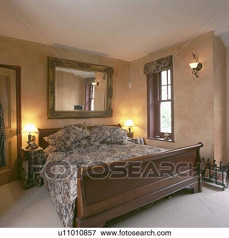 Large Mirror Above Sleigh Bed In Bedroom With Marbled Paint Effect On The Walls And Lighted Lamps Either Side Of