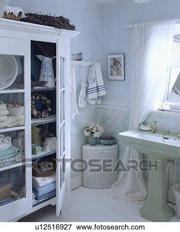 Lloyd Loom Corner Laundry Basket And Pale Green Pedestal Basin In Pastel Blue Bathroom With Painted White Cupboard Stock Photo U12516927 Fotosearch