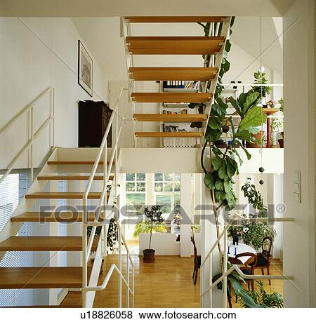 Metal And Wood Staircase With Open Treads In Modern White Hall With Wooden Flooring Stock Photo