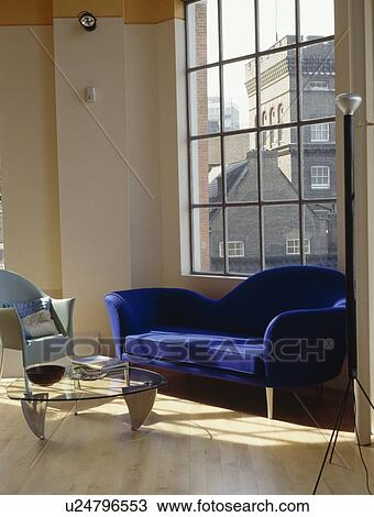 Modern blue sofa in front of large window in living room in ...