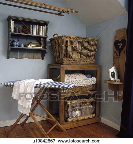 Old Wooden Ironing Board And Large Baskets On Wooden