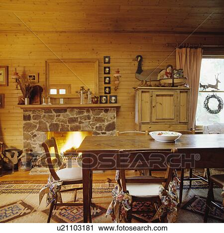 Old wooden table and chairs in dining room with stone fireplace and wood  walls Stock Image