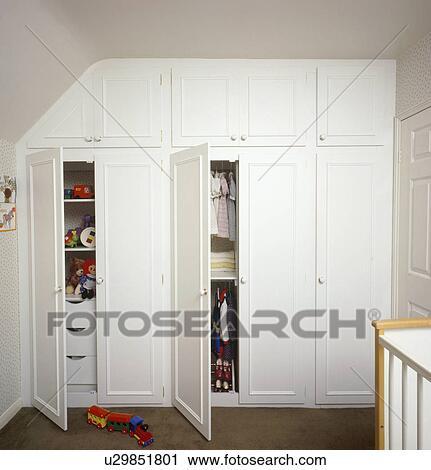 Open Deuren Op Gepaste Opslag Kasten In Kinderen Witte Slaapkamer Stock Afbeelding