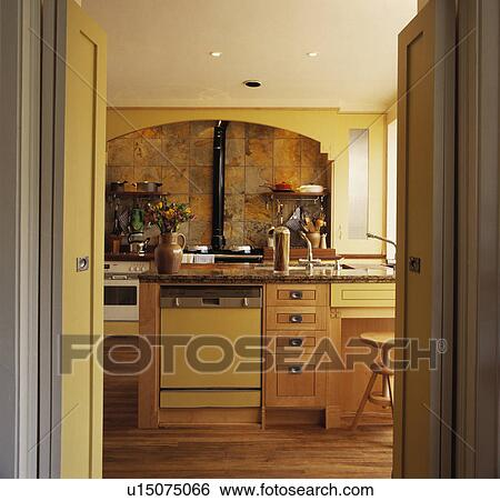 Open Doorway To Pastel Yellow Kitchen With Dishwasher In Island Unit