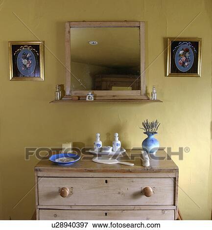 oud dennenboom spiegel boven oud dennenboom ladenkast in pastel gele slaapkamer