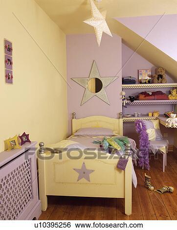 pastel gele en mauve star themed slaapkamer van het kind met ster spiegel en beweeglijk en aftekenmal op houten bed