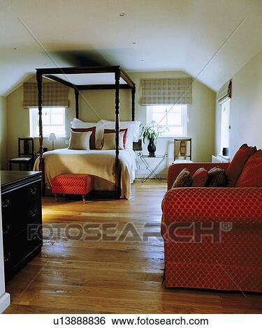 Rouges Sofa Dans Grand Blanc Grenier Chambre à Coucher à Simple Lit Baldaquin Et Plancher Bois Banque De Photographies