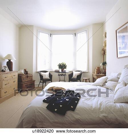 Schwarz & weiß, jacke, bett, mit, weiß, bedlinen, in, weiß, schalfzimmer,  mit, weiß, feste jalousie, und, korbgeflecht, brüste Stock Bild