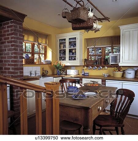 Starożytny Sosna Stół I Krzesła Poniżej Drewniany Ruina W Mały żółty Chata Kuchnia Z Biały Dopasowany Kredensy Bank Zdjęć