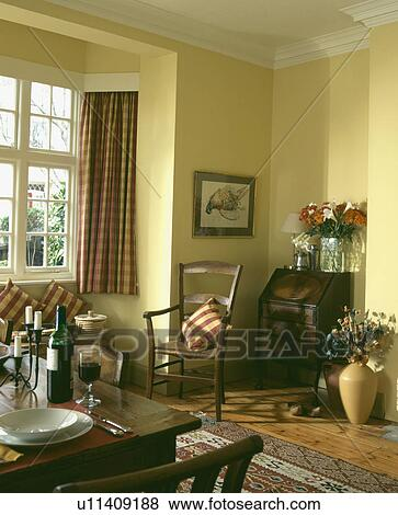Table Set For Lunch In Pale Yellow Dining Room With Patterned Red Curtains And Cushions Stock Photo