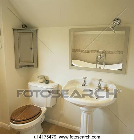 Stock Photograph Toilet And Pedestal Basin Below Mirror In Traditional Cream Bathroom Fotosearch