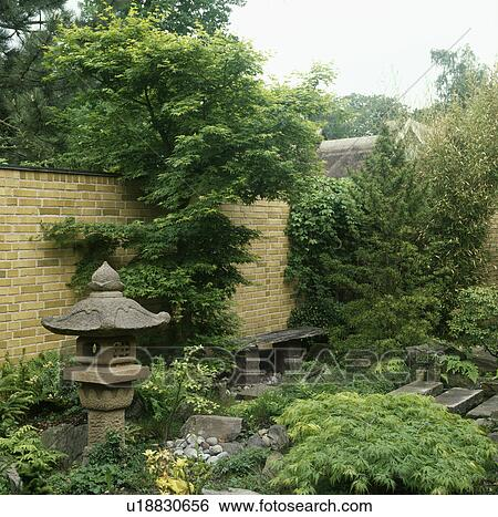 Stock Photograph   Tree And Japanese Stone Lantern In Oriental Style Green  Garden In Summer