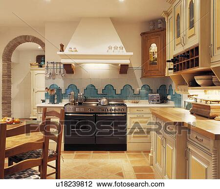 Stock Photo   Turquoise And White Wall Tiles Above Black Range Oven In  Neutral Spanish Kitchen