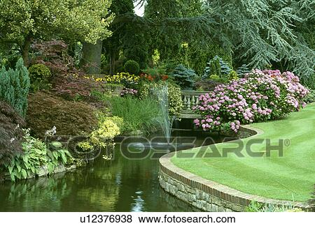 Beelden fonteinen in groot gebogen vijver in formele land tuin met roze hydrangeas - Formele meubilair ...