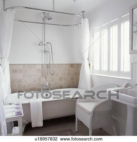 Stock Photo   White Curtains On Oval Shower Rail Above White Clawfoot Bath  In White Bathroom