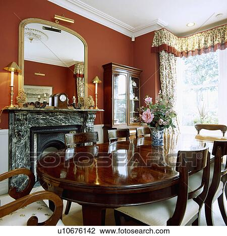 Antique Mahogany Table And Chairs In Red Dining Room With Gilt Mirror Above  Black Marble Fireplace