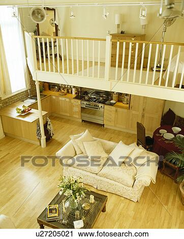 Bedroom On Mezzanine Above Kitchen And Dining Room And Living Room With Large Cream Sofa On Wooden Flooring Stock Image U27205021 Fotosearch