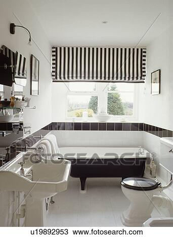 Black White Striped Blind Above Rolltop Bath In Bathroom With Tiled Border On Wall