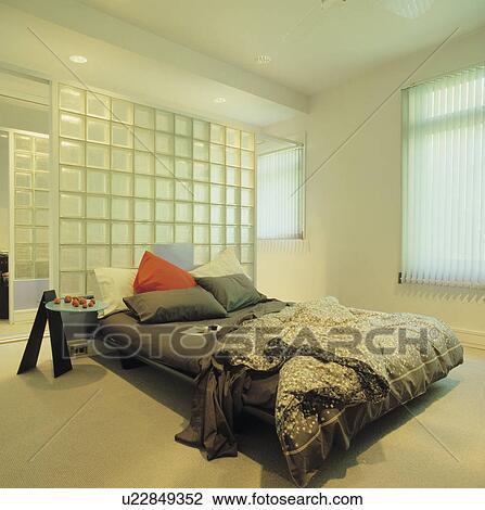 Glas ziegelstein, wand, hinter, bett, mit, schwarz, blätter, und,  nachgebildet, monochrom, federbett, in, modernes, weiß, schalfzimmer Stock  Bild