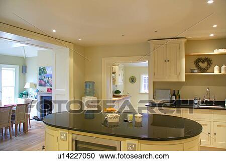 Isola, unità, con, nero, granito, worktop, in, crema, cucina, con,  passaggio ad arco, a, sala da pranzo Archivio Immagini