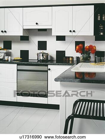 Large Black White Tiles On Wall Above Oven In Modern White Kitchen With White Floor Tiles Stock Image U17316990 Fotosearch
