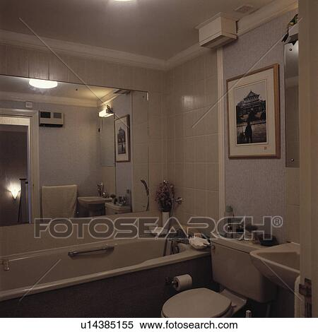 Stock Image of Large mirror above bath in small bathroom with beige ...