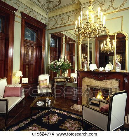 Ornate Chandelier And Gilt Cornice In Traditional Living Room
