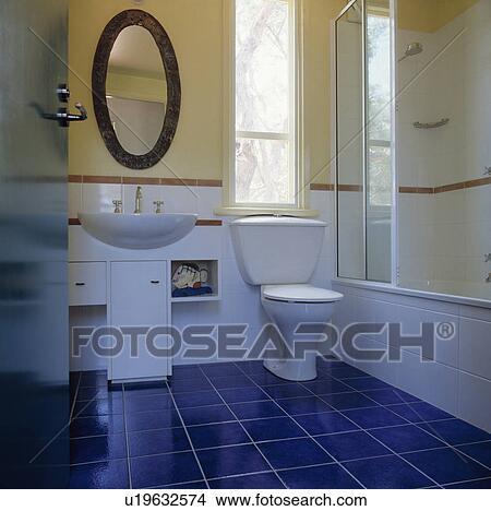 Bagno Con Mattonelle Blu.Ovale Specchio Sopra Bacino In Andato Bene Vanita Unita Accanto Gabinetto In Moderno Bagno Con Blu Mattonelle Pavimento Immagine