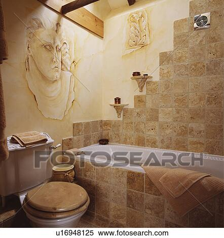 Painted Classical Head On Wall In Bathroom With Travertine Tiles Bath Panel And