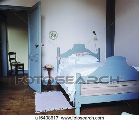 Pastel Bleu Peint Lit Bois Dans Simple Blanc Pays Chambre à Coucher à Plancher Bois Et Pastel Porte Bleue Banque De Photo