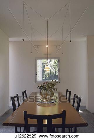 Rectangular Table Below Suspended Lighting In Modern White Dining Room