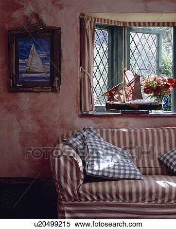 Red+white striped sofa below window in cottage living room ...