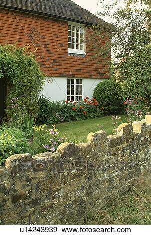 Stone Wall In Front Of Country Cottage Garden Stock Photo