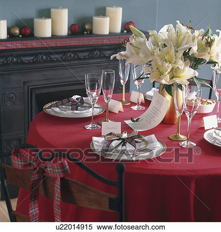 Tabla Puesto Para Cena De Navidad Con Blanco Loza En Mantel Rojo Y Arreglo Floral De Blanco Lirios Banco De Fotografías