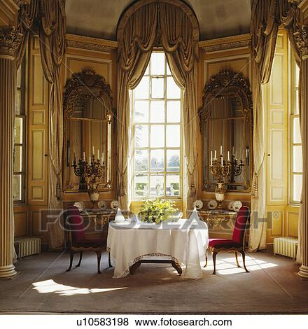 White Cloth On Table In Georgian Dining Room With Antique Mirrors And Swagged Curtains At Tall Windows Stock Photo U10583198 Fotosearch
