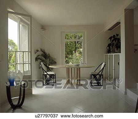 Picture White Tiled Floor In Uncluttered Dining Room With Oval Table And Black Chairs