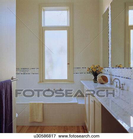 Picture of Window above bath in modern bathroom with basin set into on bathroom window above vanity, bathroom window above shower, bathroom window above door, bathroom recessed lighting, kitchen above sink,