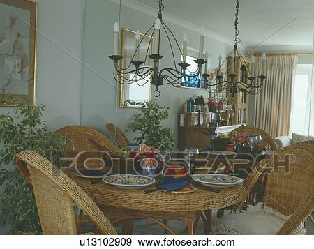 Wrought Iron Chandelier Above Wicker Table And Chairs In Dining Room With Mirrored Wall Stock Photo U13102909 Fotosearch