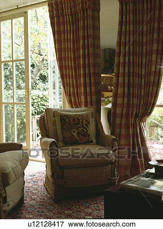 Beige armchair in front of red checked curtains at French doors in country  living room Stock Photo