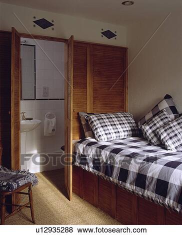efb58dad4336 Black+white, comprobado, colcha, y, cojines, cama, delante de, de madera,  louvre, puertas, a, pequeño, ensuite, cuarto de baño