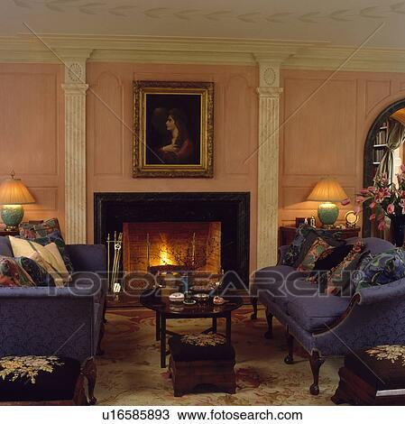 Blue sofas in traditional living room with picture above fireplace Stock  Image