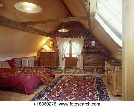bluered oosters tapijt op houtenvloer in groot zoldertjes slaapkamer met witte gordijnen en rood dekbed
