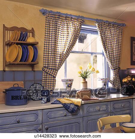 stock foto blue yellow kariert vorh nge auf fenster in pastell gelb kueche mit. Black Bedroom Furniture Sets. Home Design Ideas