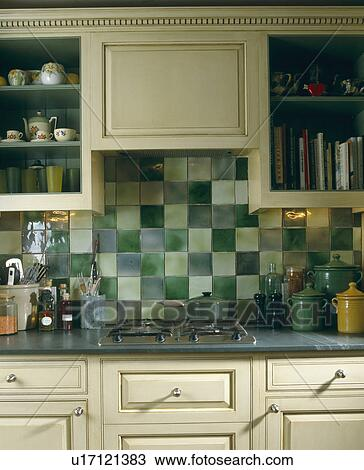 Close Up Of Green Wall Tiles Above Hob Built In To Kitchen Worktop Cream