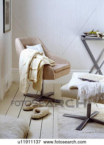 Surprising Cream Throw On Beige Swivel Chair With Footstool In Corner Gmtry Best Dining Table And Chair Ideas Images Gmtryco
