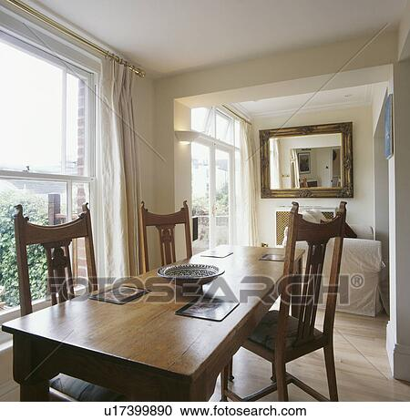 Dining Room Extension With Cream Curtains And Pale Wood Table And Chairs