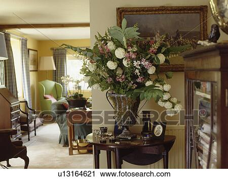 Large Floral Arrangement In Urn On Antique Console Table In Cottage Living  Room
